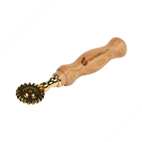 Golden brass pasta cutter with single toothed blade. Chestnut wood handle