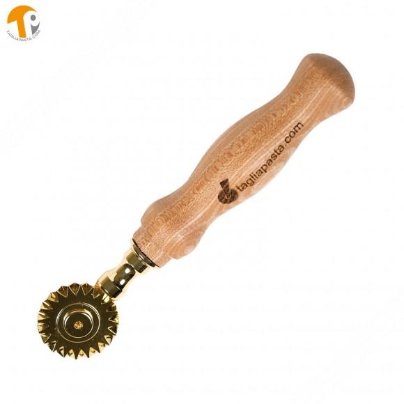 Rotella tagliapasta in ottone bagnato in oro con lama singola dentata. Manico in legno di olmo