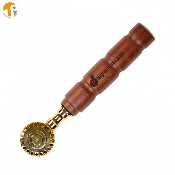 Rotella tagliapasta in ottone bagnato in oro con lama singola dentata. Manico in legno di amaranto