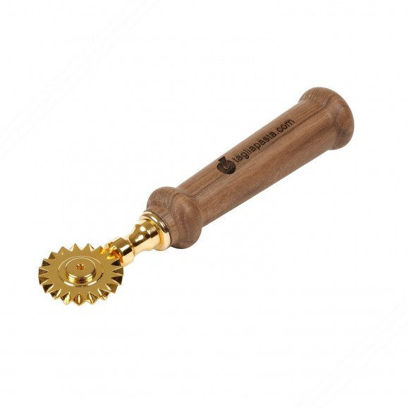 Golden brass pasta cutter with single toothed blade. Walnut wood handle