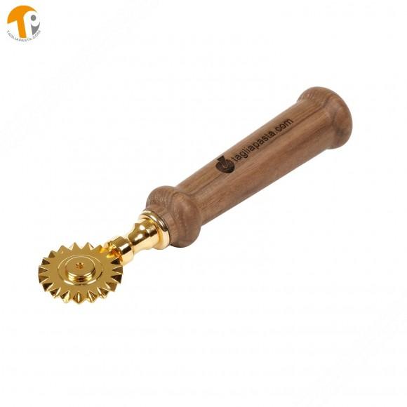 Rotella tagliapasta in ottone bagnato in oro con lama singola dentata. Manico in legno di noce