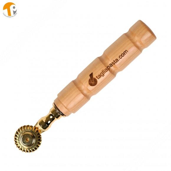 Rotella tagliapasta in ottone bagnato in oro con lama singola dentata. Manico in legno di acero