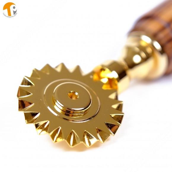 Rotella tagliapasta in ottone bagnato in oro con lama singola dentata. Manico in legno di teak