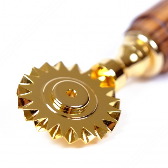Golden brass pasta cutter with single toothed blade. Ash wood handle