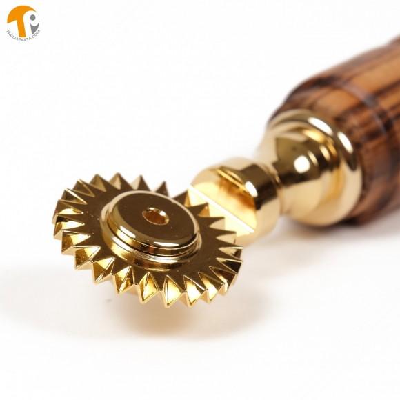 Rotella tagliapasta in ottone bagnato in oro con lama singola dentata. Manico in legno di doussé
